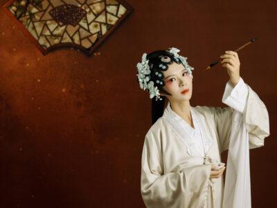 漢服で筆を持つ女性の写真