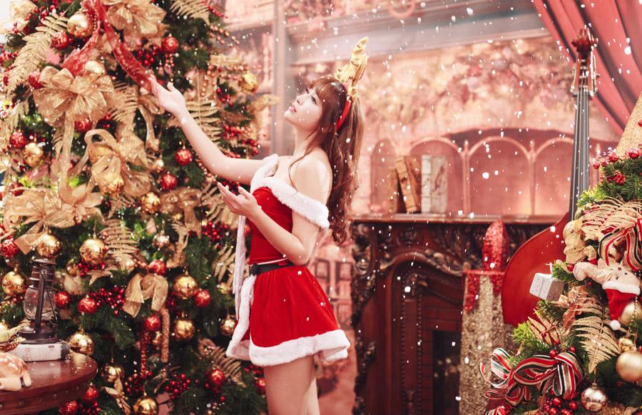 サンタのコスプレでクリスマスツリーに触る台湾人女性
