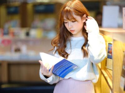 本棚と英語の本を読む台湾人女性