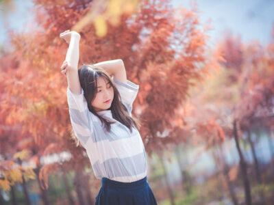 紅葉を背景に背伸びをする台湾人女性