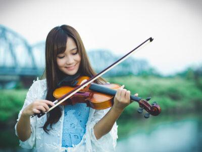 鉄橋のある川辺でバイオリンを弾く台湾人女性