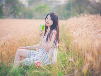 パックの飲み物を持って畦道に座る台湾人女性の写真