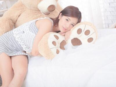 テディベアとベッドで寝る台湾人女性